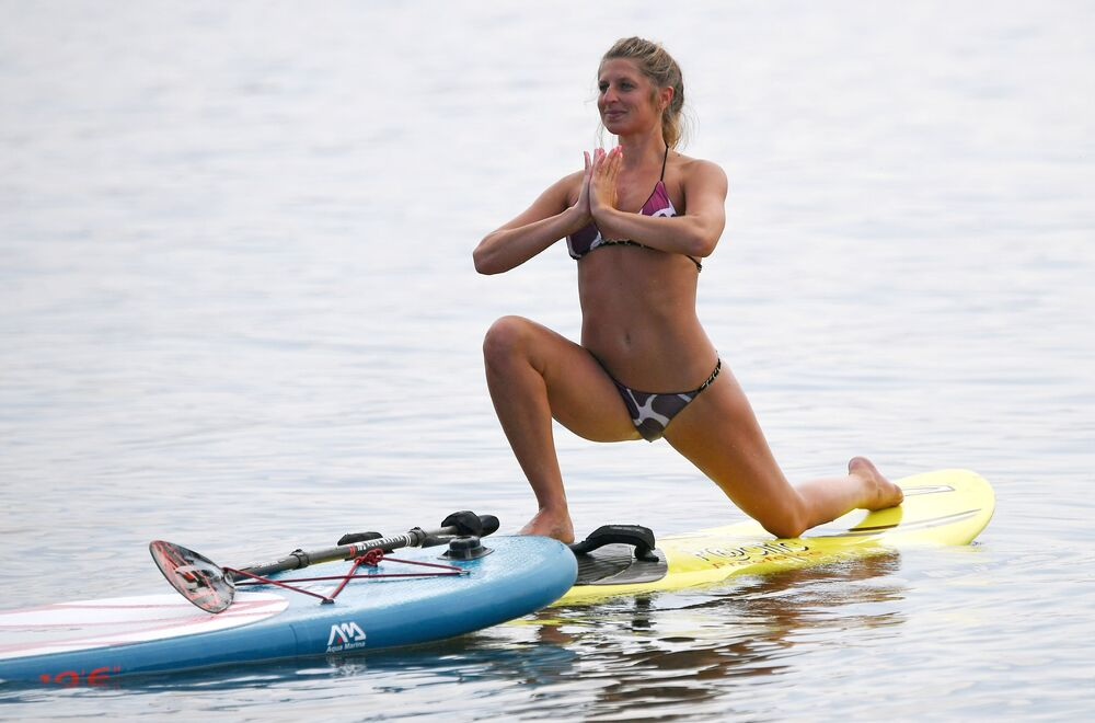 Russian athlete Yuliya Boyarintseva practices yoga on a sup-board in Russia's Siberia.