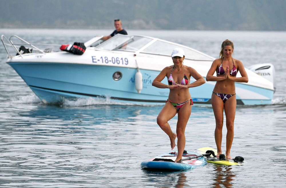 Russian athlete Yuliya Boyarintseva holds a sup-board yoga session with her student in the Yenisei River.