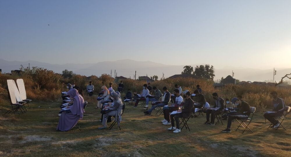 Students make space for themselves on the unkept ground with tall grasses and bushes in the open-air classroom in Srinagar