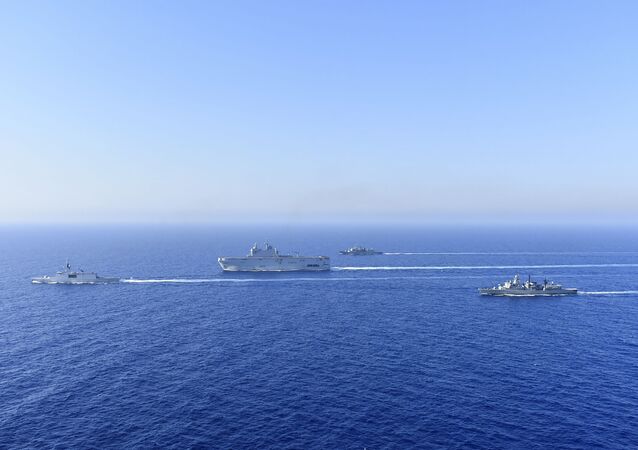 In this photo provided by the Greek National Defence, a French Tonnerre helicopter carrier, center, and French Lafayette frigate, left, are escorted by Greek and French military vessels during a maritime exercise in the Eastern Mediterranean, Thursday, Aug. 13, 2020