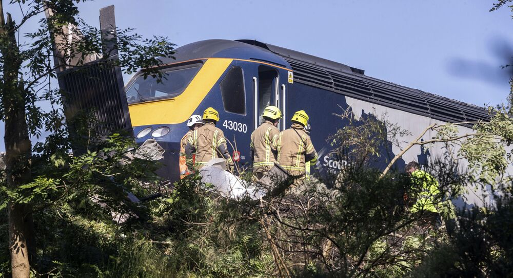 Emergency services attend the scene of a derailed train in Stonehaven, Scotland, Wednesday Aug. 12, 2020
