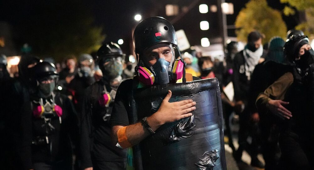 A protesters slaps his shield while marching toward the Portland Police Bureau North Precinct on the 75th day of protests against racial injustice and police brutality on August 10, 2020 in Portland, Oregon. Crowd sizes began growing again last week as protesters regularly march on city and county law enforcement buildings.