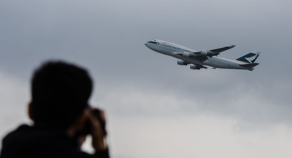 This file photo taken on March 15, 2017 shows an aviation enthusiast photographing a Cathay Pacific cargo aircraft as it takes off from the international airport in Hong Kong. - Troubled Hong Kong carrier Cathay Pacific said it lost 1.27 billion USD in the first half of this year, the latest major airline to reveal how badly the COVID-19 coronavirus pandemic has eviscerated its business.