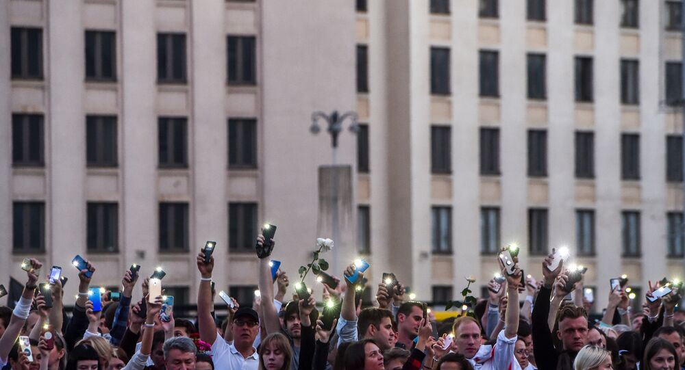 Demonstrators raise their mobile phones near the Government House in Independence Square during a protest rally against police violence during at rallies of opposition supporters, who accuse strongman Alexander Lukashenko of falsifying the polls in the presidential election, in central Minsk on August 14, 2020. - Crowds of workers walked off the job on August 14, 2020, at several factories in Belarus's capital Minsk in support of the opposition calling for leader Alexander Lukashenko to step down. Hundreds of workers marched from the Minsk Automobile Plant (MAZ) and the Minsk Tractor Works (MTZ) after the opposition called for strikes against Lukashenko's disputed claim to have won re-election.