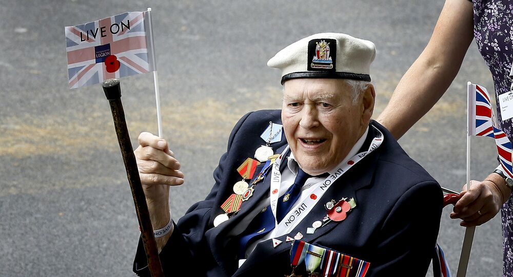 A veteran waves a flag during the parade to commemorate VJ day, as it passes along Whitehall in London, Saturday, Aug. 15, 2015. The parade, comprised of veterans of the Far East Campaign, their families and descendants, led by Pipes and Drums drawn from the Army, was to mark the 70th anniversary of the victory over Japan during World War II.