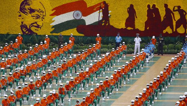 People dressed in the colors of the Indian national flag listens to Prime Minister Narendra Modi speaking from the ramparts of the historic Red Fort monument on Independence Day in New Delhi, India, Saturday, Aug. 15, 2020. (AP Photo/Manish Swarup) - Sputnik International