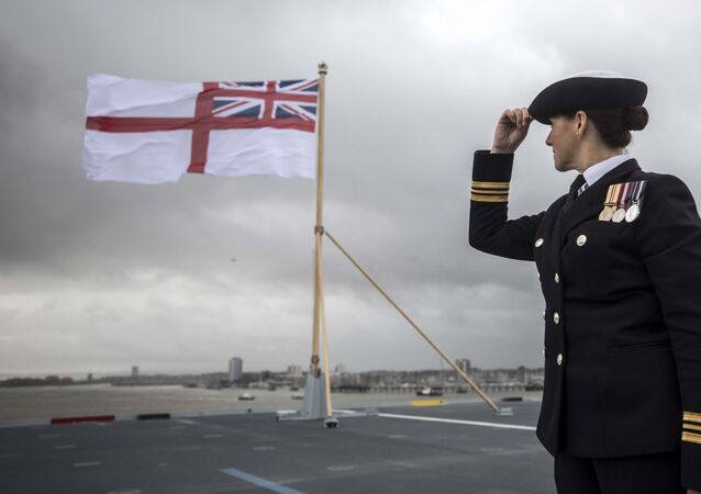 A naval officer looks up at the fluttering White ensign flag hoisted at the stern during the Commissioning Ceremony for the Royal Navy aircraft carrier HMS Queen Elizabeth at HM Naval Base in Portsmouth, southern England on December 7, 2017.