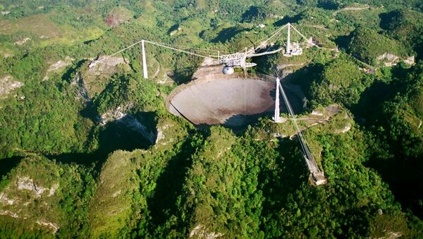 The world's largest radio telescope is seen from the air in this Wednesday, 26 March 2003 photo at the Arecibo Observatory, Puerto Rico - Sputnik International