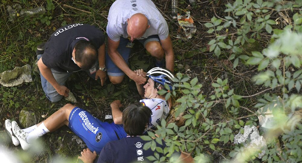 Cyclist Remco Evenepoel receives first aid after falling during the Tour of Lombardy cycling race, from Bergamo to Como, Italy, Saturday, Aug. 15, 2020.