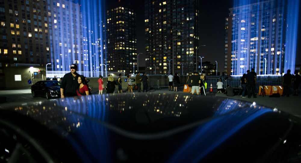 People watch the Tribute in Light at lower Manhattan, Wednesday, Sept. 11, 2019, in New York. Each year the city shines the powerful columns of light into the sky from Lower Manhattan to represent the fallen twin towers of the World Trade Center.