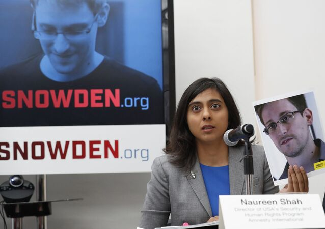 Naureen Shah, director of Amnesty International USA's Security & Human Rights Program, holds up a photo of Edward Snowden during a news conference to call upon President Barack Obama to pardon Snowden before he leaves office, Wednesday, Sept. 14, 2016, in New York. Human and civil rights organizations, including the ACLU, Human Rights Watch and Amnesty International, launched a public campaign to persuade Obama to pardon the former National Security Agency contractor, who leaked classified details in 2013 of the U.S. government's warrantless surveillance program before fleeing to Russia.