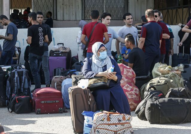 Palestinians wait to cross to the Egyptian side of Rafah border crossing after months of closure due to the coronavirus pandemic in the southern Gaza Strip, on August 11, 2020.