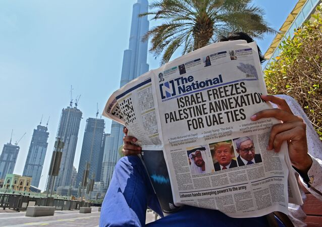 A man reads a copy of UAE-based The National newspaper near the Burj Khalifa, the tallest structure and building in the world since 2009, in the gulf emirate of Dubai on August 14, 2020, as the publication's headline reflects the previous day's news as Israel and the UAE agreed to normalise relations in a landmark US-brokered deal. - The deal marks only the third such accord the Jewish state has struck with an Arab nation, an historic shift making the Gulf state only the third Arab country to establish full diplomatic ties with the Jewish state. The Palestinian leadership voiced its strong rejection and condemnation of the deal and announced it would withdraw its envoy from the UAE, and Turkey also condemned the deal as an act of treachery.