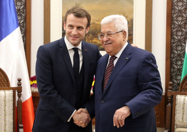 French President Emmanuel Macron (L) shakes hands with Palestinian President Mahmoud Abbas at his headquarters in the West Bank city of Ramallah, on January 22, 2020.