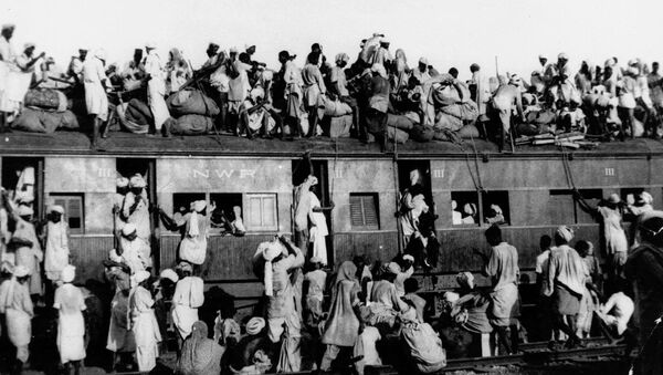 In this September 1947, file photo hundreds of Muslim refugees crowd on top a train leaving New Delhi for Pakistan. After Britain ended its colonial rule over the Indian subcontinent, two independent nations were created in its place _ the secular, Hindu-majority nation of India, and the Islamic republic of Pakistan. The division, widely referred to as Partition, sparked massive rioting that killed up to 1 million, while another 15 million fled their homes in one of the world's largest ever human migrations. (AP Photo, File) - Sputnik International