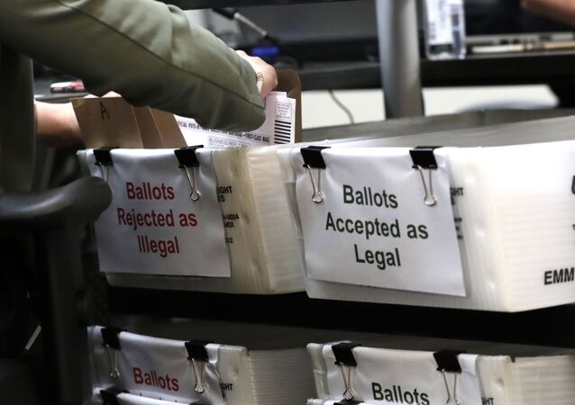 A Miami-Dade County Elections Department employee places a vote-by-mail ballot for the August 18 primary election into a box for rejected ballots as the canvassing board meets at the Miami-Dade County Elections Department, Thursday, July 30, 2020, in Doral, Fla