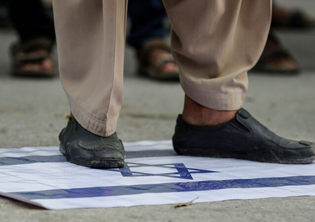 A supporter of religious and political party Jamaat-e-Islami (JI) steps on an Israeli flag to condemn the diplomatic agreement between the United Arab Emirates (UAE) and Israel, during a protest in Karachi, Pakistan August 16, 2020.