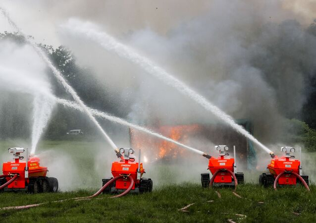 Remotely controlled robotic fire fighting equipment extinguish a mock fire during a drill in Kolkata, India, Thursday, Aug. 6, 2020