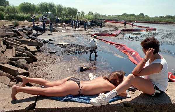 Sunbathers watch workers clean up oil spilled on the resort beach of Playa Nueva in Magdalena, Argentina, 100 km (62 miles) south of Buenos Aires, 21 January 1999. - Sputnik International
