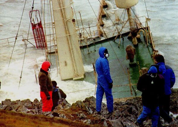 Members of the media with masks on their faces watch the wreckage of the oil tanker Braer that ran aground during a storm off Shetland, Scotland, in January 1993 and broke up a week later following storm force winds. - Sputnik International