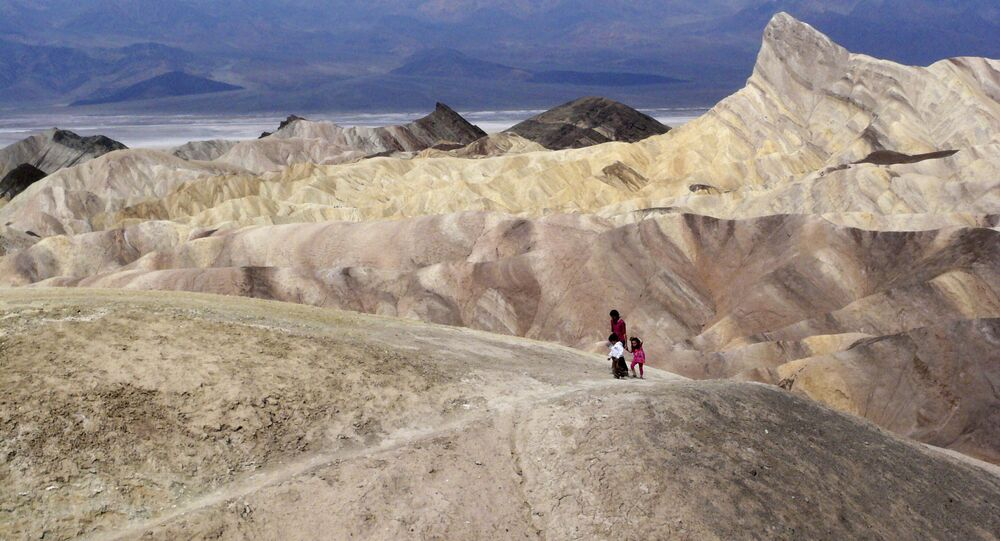 In this April 11, 2010, file photo, tourists walk along a ridge at Death Valley National Park, Calif.