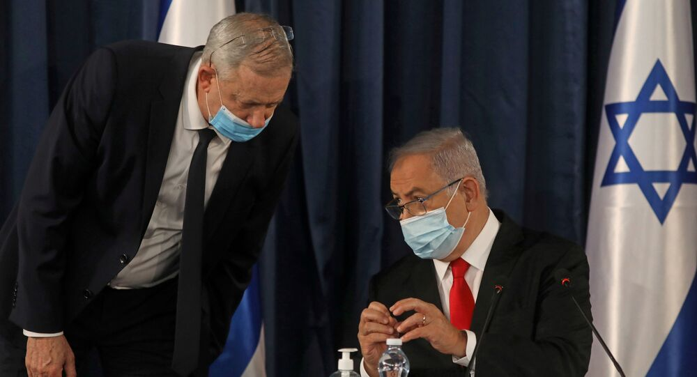 FILE PHOTO: Israeli Prime Minister Benjamin Netanyahu speaks with Alternate Prime Minister and Defence Minister Benny Gantz, as they both wear a protective mask due to the ongoing coronavirus disease (COVID-19) pandemic, during the weekly cabinet meeting in Jerusalem June 7, 2020