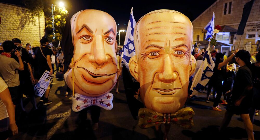 Demonstrators wear masks depicting Israeli Prime Minister Benjamin Netanyahu and Israel's Alternate Prime Minister and Defence Minister Benny Gantz during a protest against Israeli Prime Minister Benjamin Netanyahu's alleged corruption and economic hardship stemming from lockdown during the coronavirus disease (COVID-19) crisis, near his residence in Jerusalem August 8, 2020