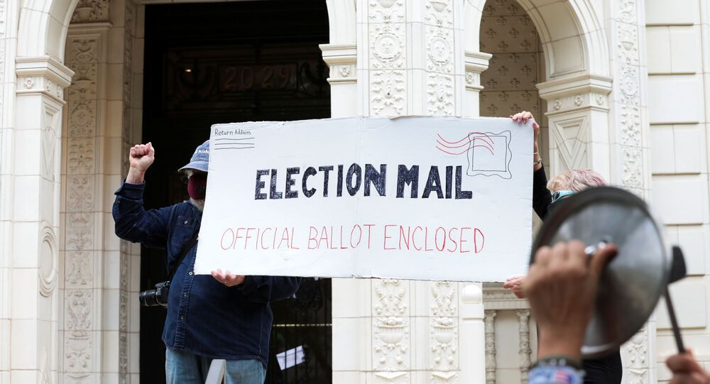 Demonstrators hold a large mock mail-in ballot as others hit pans and pots during a protest against changes in the postal service outside of the condo of Postmaster General Louis DeJoy, as the spread of the coronavirus disease (COVID-19) continues, in Washington, U.S., August 15, 2020.
