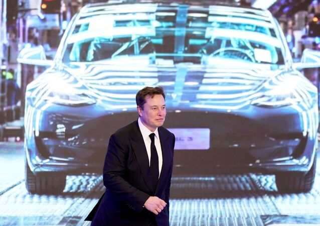 Tesla Inc CEO Elon Musk walks next to a screen showing an image of Tesla Model 3 car during an opening ceremony for Tesla China-made Model Y program in Shanghai, China January 7, 2020