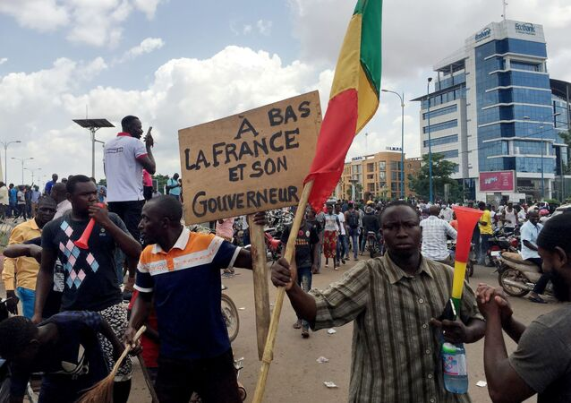 Opposition supporters react to the news of a possible mutiny of soldiers in the military base in Kati, outside the capital Bamako, at Independence Square in Bamako, Mali August 18, 2020.