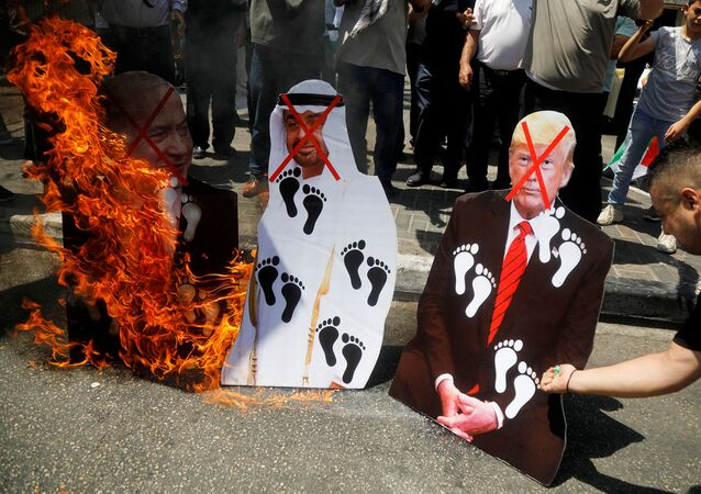 Palestinians burn cutouts depicting U.S. President Donald Trump and Abu Dhabi Crown Prince Mohammed bin Zayed al-Nahyan and Israeli Prime Minister Benjamin Netanyahu during a protest against the United Arab Emirates' deal with Israel to normalise relations, in Nablus in the Israeli-occupied West Bank August 14, 2020.