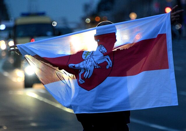 A Belarus opposition supporter holds a flag during a rally on the Independence Square, in Minsk, Belarus