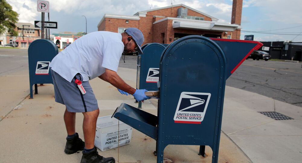 A United States Postal Service (USPS) worker handles the mail in a drop-off box behind a post office in Oak Park, Michigan, U.S.  August 17, 2020