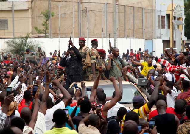 A crowd of people cheer Malian army soldiers at the Independence Square  in Bamako
