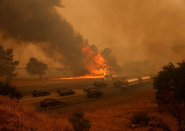 Vehicles are seen along Interstate 80 as flames from the LNU Lighting Complex Fire are seen on both sides on the outskirts of Vacaville, California, 19 August 2020