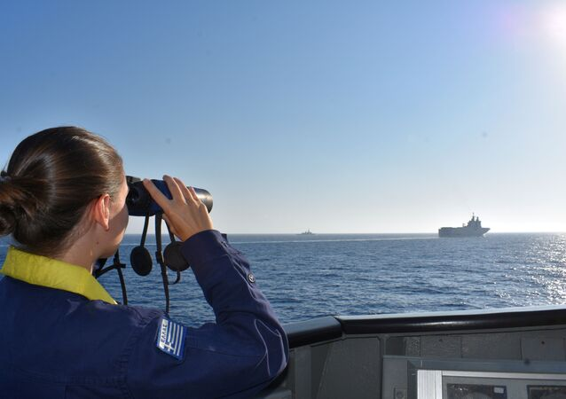 A woman looks through binoculars as Greek and French vessels sail in formation during a joint military exercise in Mediterranean sea, in this undated handout image obtained by Reuters on August 13, 2020