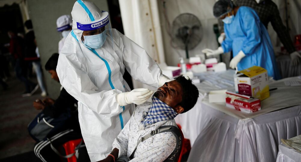A healthcare worker wearing personal protective equipment (PPE) takes a swab from a migrant worker who returned to Delhi from his native state, for a rapid antigen test at a bus terminal, amidst the coronavirus disease (COVID-19) outbreak in New Delhi, India, 17 August 2020