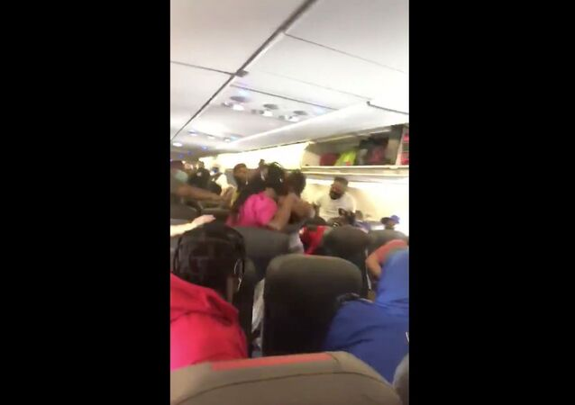 Cellphone recording captures moment in which an all-out brawl broke out on American Airlines flight 1665 after a passenger refused to wear a face mask, in line with the airline's policies.