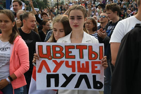 A woman holds a banner with Flowers are better than bullets written on it during a rally in Minsk, Belarus on 15 August, 2020. - Sputnik International
