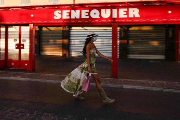 A woman wearing a face mask walks past the closed Le Cafe Senequier situated along the Quai Jean Jaures, on the Saint-Tropez harbour on 16 August 2020, as the city made wearing a protective mask mandatory in the town centre due to a resurgence of the coronavirus.   - Sputnik International