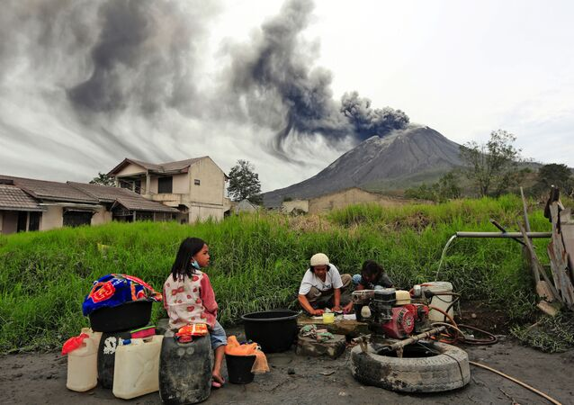 Villagers do their laundry as Mount Sinabung spews volcanic materials during an eruption, in Karo, North Sumatra, Indonesia Friday, Aug. 14, 2020.