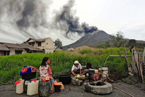 Villagers do their laundry as Mount Sinabung spews volcanic materials during an eruption, in Karo, North Sumatra, Indonesia Friday, 14 August 2020.  - Sputnik International