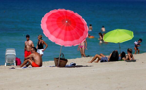 People sunbathe and swim on El Arenal beach, amid the outbreak of the coronavirus disease (COVID-19), in Palma de Mallorca, Spain, 15 August 2020.  - Sputnik International