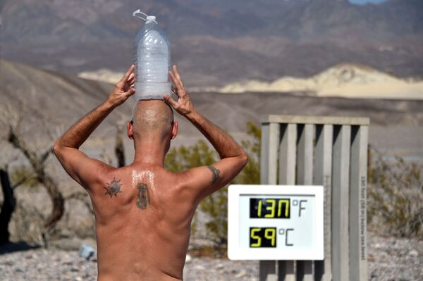 Steve Krofchik of Las Vegas keeps cool with a bottle of ice on his head as the thermometer reads 130 degrees Fahrenheit (54.4 Celsius) at the Furnace Creek Visitors Centre in Death Valley, California, 17 August 2020.  - Sputnik International