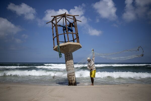 A Palestinian fisherman cleans up his fishing net after the Israeli decision to close Gaza's fishing zone, on the beach in Gaza City, Tuesday, 18 August 2020.  - Sputnik International