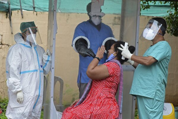 A health worker wearing personal protective equipment (PPE) collects a swab sample from a woman at a free COVID-19 coronavirus testing centre in Hyderabad on 19 August 2020.  - Sputnik International