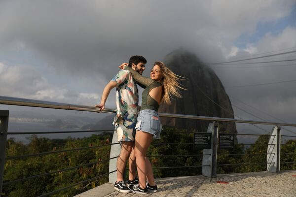 A couple stands with Sugarloaf Mountain in the background during reopening after a months-long closure due to the outbreak of the coronavirus disease (COVID-19), in Rio de Janeiro, Brazil, 15 August 2020.  - Sputnik International