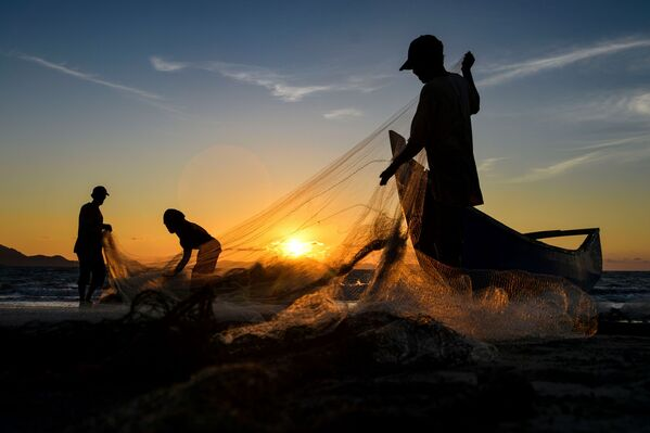 Fishermen clean their nets after fishing at sunset in Banda Aceh, Sumatra, Indonesia, on 19 August, 2020. - Sputnik International