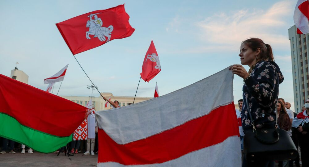 A woman holds a historical white-red-white flag of Belarus during an opposition demonstration against presidential election results at the Independence Square in Minsk, Belarus August 22, 2020.