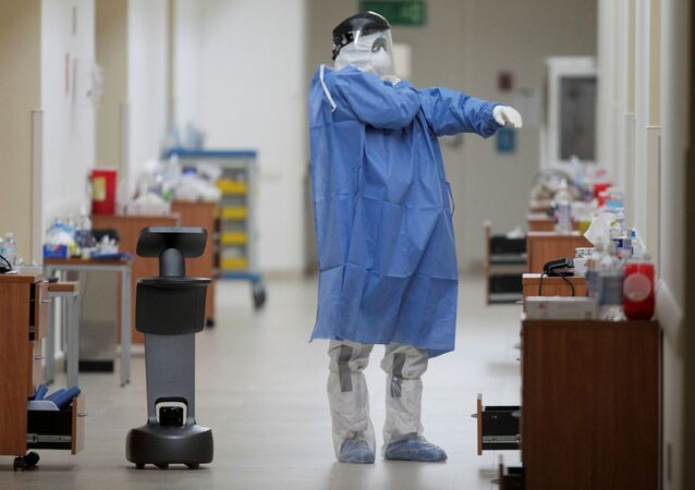 A healthcare worker puts on his protective suit while using a robot to carry out consultations with patients suffering from the coronavirus disease (COVID-19), at NOVA hospital in Monterrey, Mexico August 18, 2020.